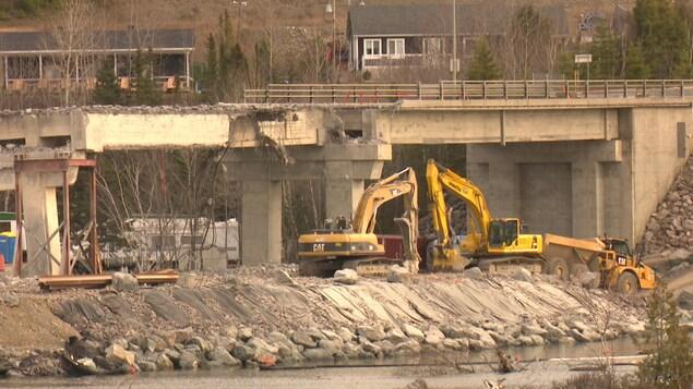 Des camions travaillent près de la structure qui est démolie.
