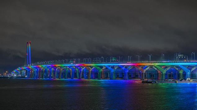 Le pont Samuel-de Champlain, le soir, éclairé avec des lumières aux couleurs de l'arc-en-ciel.