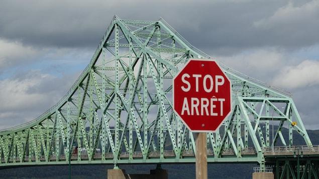Un panneau d'arrêt avec le pont J.-C. Van Horne en arrière plan.