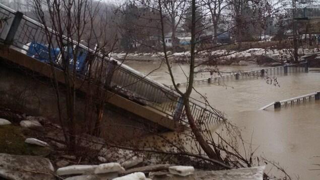 Un camion bloqué sur un pont effondré dans une rivière.