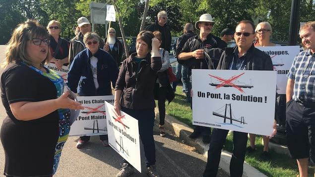 Des manifestants réclament un pont à Tadoussac pancartes à la main.