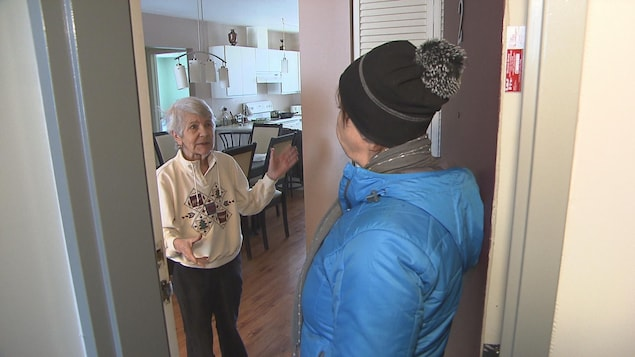 Une bénévole du réseau panquébécois des popotes roulantes rencontre une bénéficiaire.