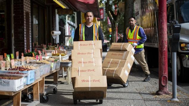 Deux livreurs poussent des boîtes de porc empilés sur des chariots devant une épicerie.