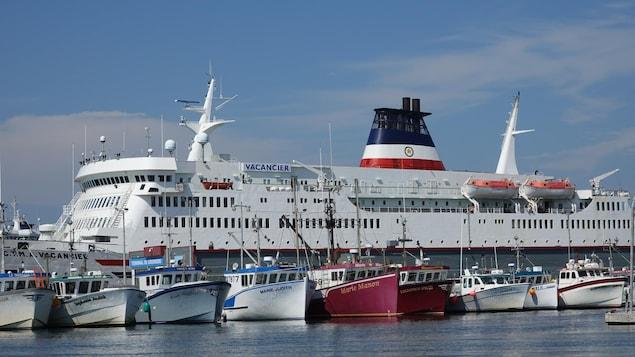 Le CTMA Vacancier et plusieurs petits bateaux de pêche en avant-plan au port de Cap-aux-Meules.