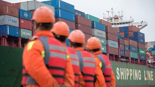 Des travailleurs regardent un cargo s'approcher d'un terminal au port de Qingdao dans le Shandong.