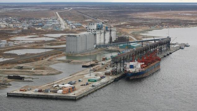 Vue aérienne d'un port avec un grand navire-cargo et des silos à grain, au beau milieu d'un paysage de toundra, en été.