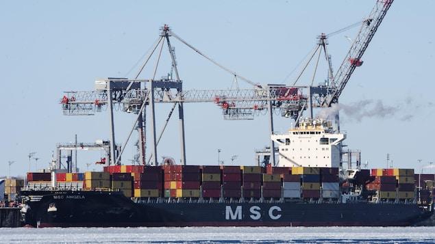 Un bateau qui transporte des conteneurs est entrain d'être déchargé par des grues.