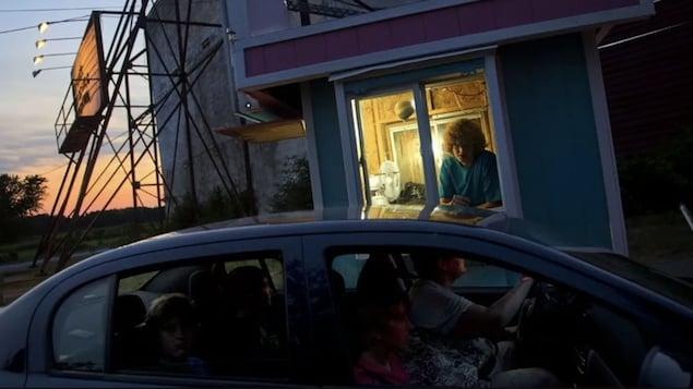 Une voiture commande un ticket au box office d'un ciné-parc.
