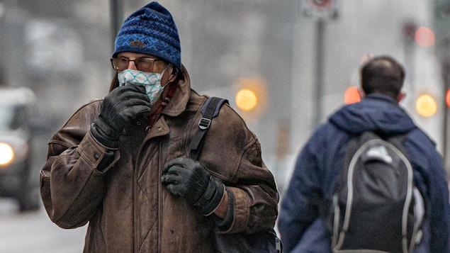 Un homme ajuste son masque, dehors, l'hiver.