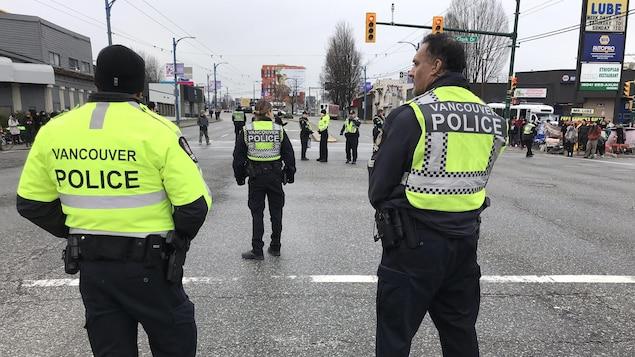 Des policiers se tiennent debout au centre l'intersection.