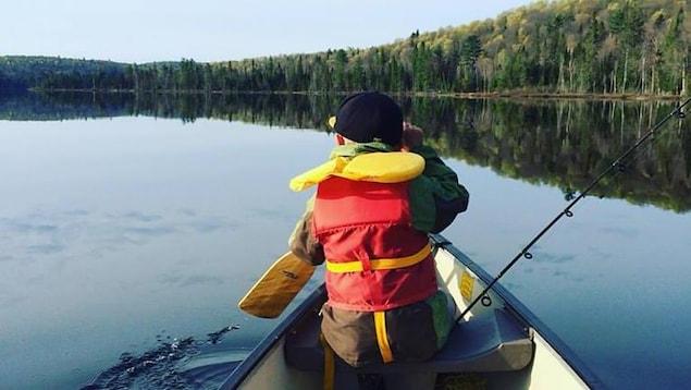 Un enfant sur une embarcation porte sa veste de flottaison.