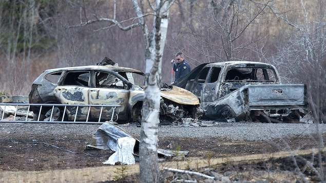 Un enquêteur entre deux véhciules complètement incendiés.