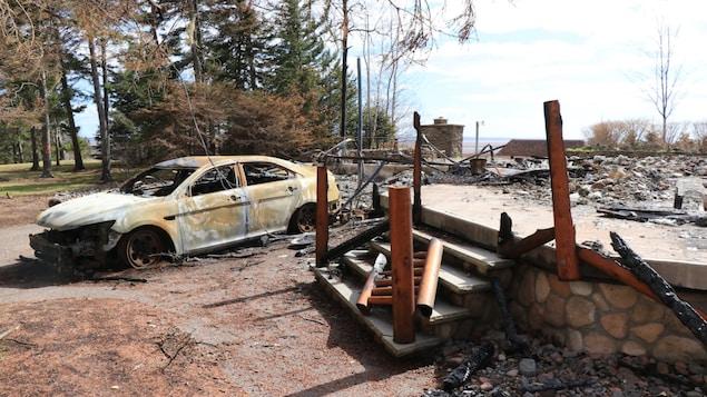 Les ruines calcinées d'un chalet et la carcasse d'une voiture incendiée.