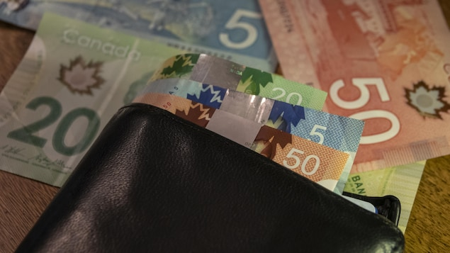 Des billets de 5 $, 20 $ et 50 $ dans un portefeuille sur une table.