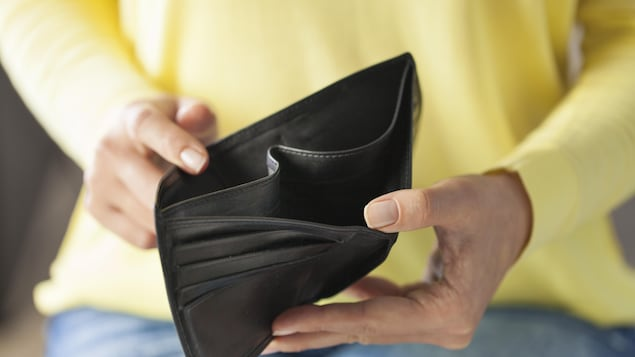 Une femme tient dans ses mains un portefeuille vide. Elle porte un pull jaune et un jean. Le portefeuille est en cuir noir.