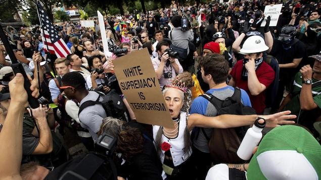 Au milieu de la foule, une manifestante tient une pancarte sur laquelle on peut lire : « Le suprémacisme blanc est du terrorisme. »