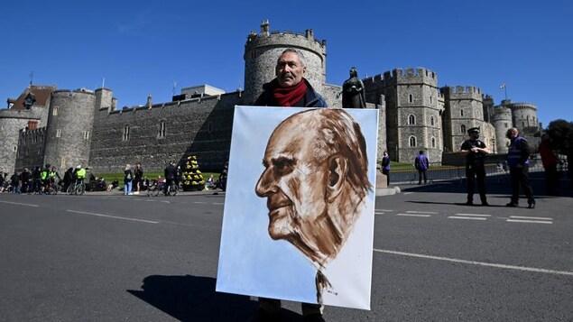 Un artiste tient dans ses bras le portrait qu'il a peint du prince Philippe.