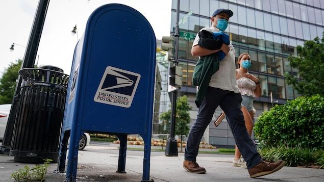 Un homme et une femme portant un masque marchent près d'une boîte postale.