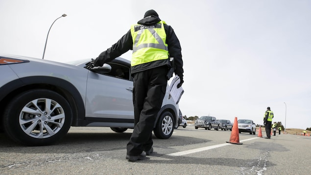 Un agent vêtu d'une veste jaune et avec des documents à la main s'approche d'une automobile.