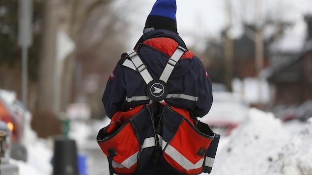 Un facteur vu du dos marche sur un trottoir enneigé