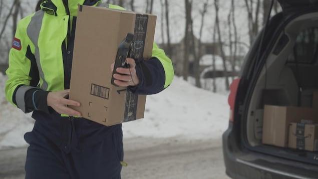 Vue rapprochée d'un facteur de Postes Canada qui transporte un paquet de moyenne grandeur dans ses bras.