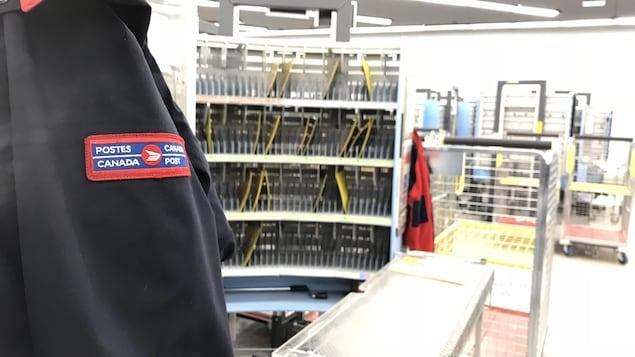 Un manteau de facteur en premier plan, un centre de distribution en arrière-plan.