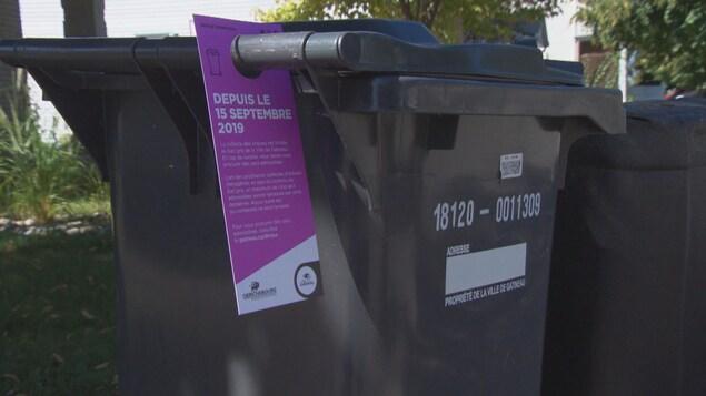 Un bac de poubelles, avec un avertissement fourni par la Ville de Gatineau.