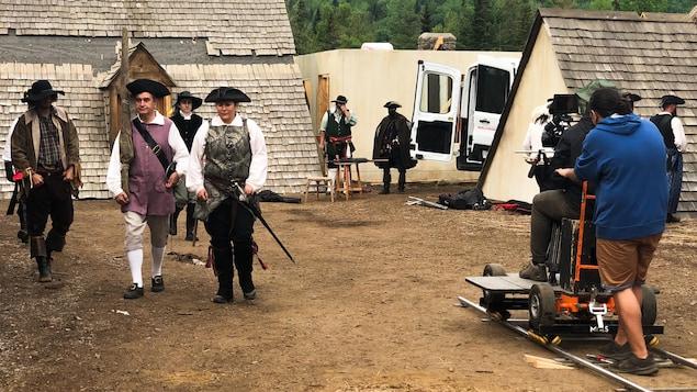 Des comédiens en costume d'époque marche sur le plate de tournage.