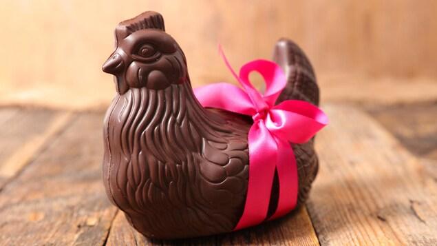 La poule en chocolat est entouré d'un ruban rose.