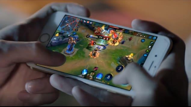 Deux mains en train de jouer à un jeu sur téléphone mobile.