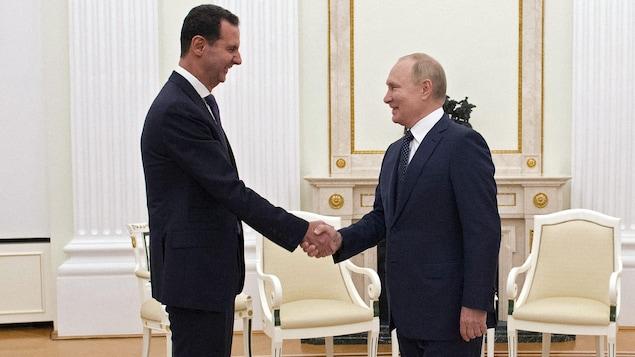 Vladimir Poutine et Bachar Al-Assad se serrant la main.