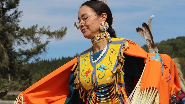 Une femme danse dans une regalia jaune et orange au pow-wow de Wemotaci.