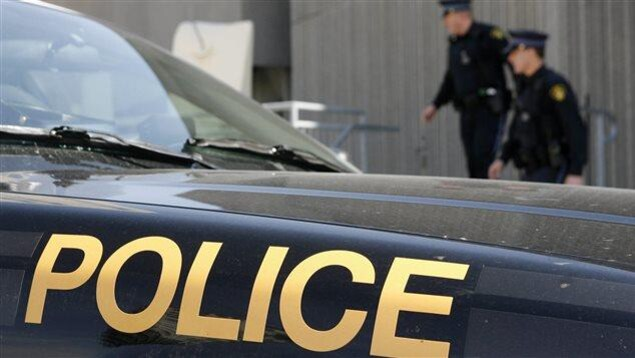 Deux agents de la police provinciale de l'Ontario derrière une autopatrouille.