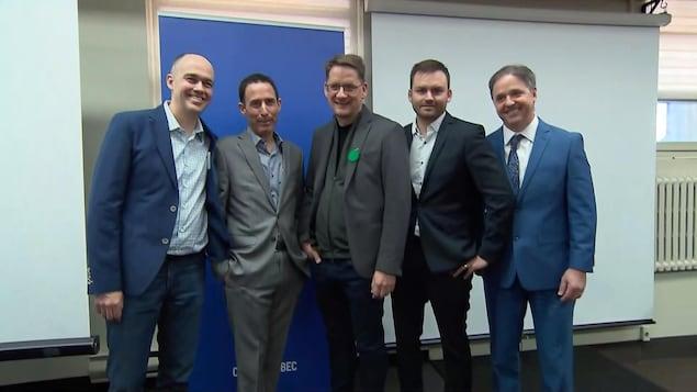 Cinq hommes en veston et cravate sourient à la caméra.