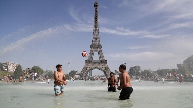 Des garçons jouent au ballon dans une fontaine devant la tour Eiffel.
