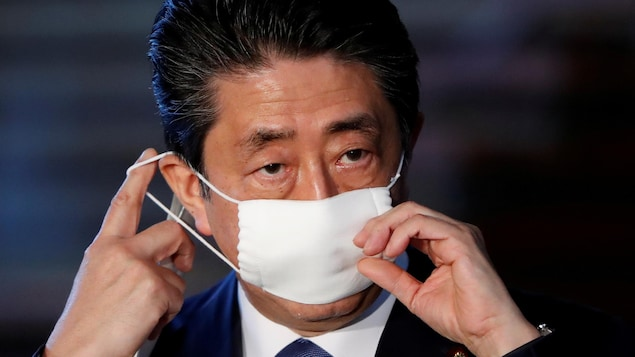 Shinzo Abe ajuste son masque de protection.