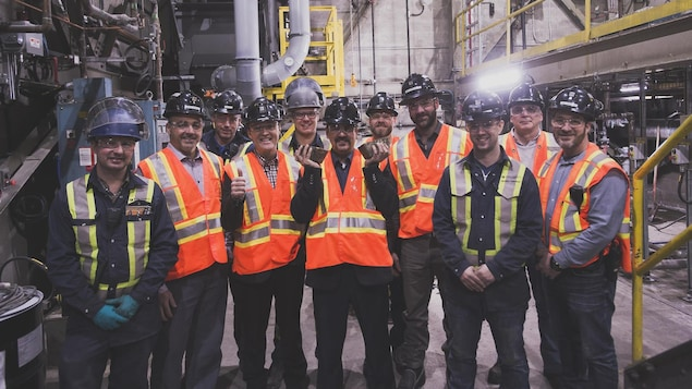 Une équipe de mineurs pose avec deux lingots d'or, dans une usine.