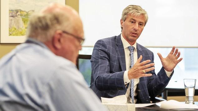 Tim Houston et Robert Strang sont assis à une table de réunion et discutent.