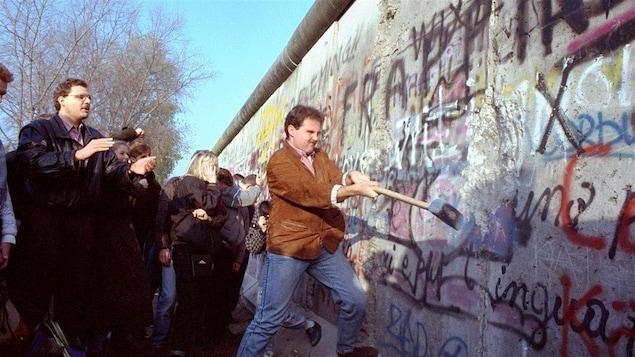 Un homme tente de faire tomber une partie du mur de Berlin, le 12 novembre 1989.