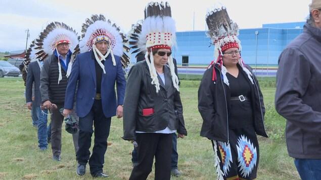 Plusieurs membres des Premières Nations portant des coiffes traditionnelles marchent les uns derrière les autres.