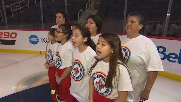 Des enfants et une adulte chantent sur une patinoire de hockey.