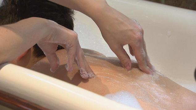 Les mains de la préposée sur le dos de la personne dans son bain.