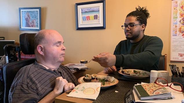 Robert Labrecque se fait nourrir par son préposé à la table de cuisine