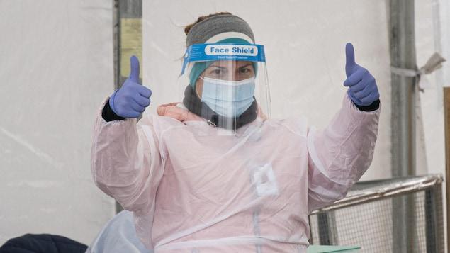 Une préposée de la santé avec son masque et sa combinaison lève les deux pouces.