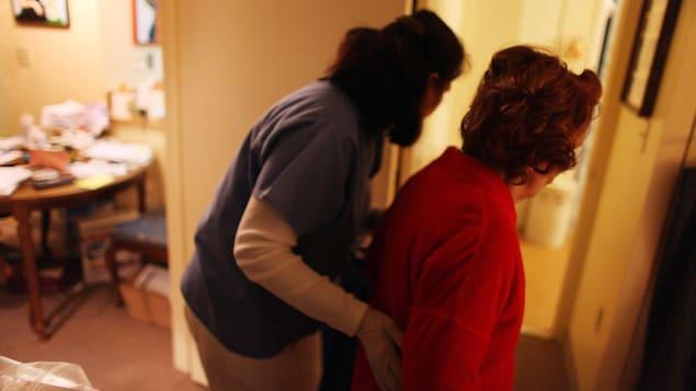 Une préposée aux bénéficiaires aidant une aînée à marcher.