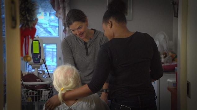 Deux préposées aux bénéficiaires discutent avec une dame âgée au CHSLD.