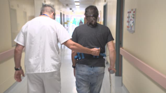 Un préposé aide un homme à marcher dans un couloir.