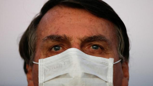 Jair Bolsonaro regarde au loin, masque au visage.