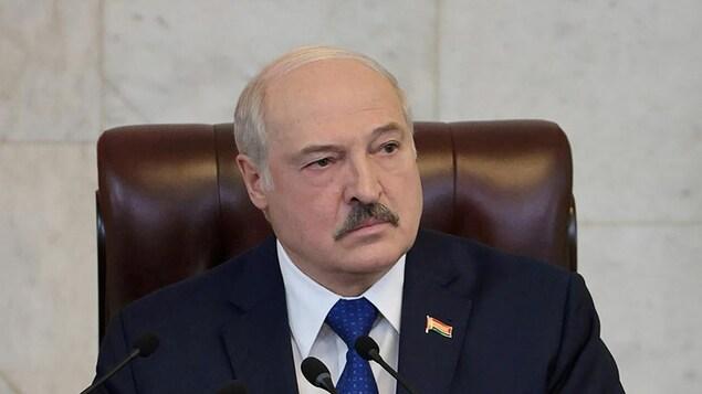 Alexander Loukachenko est assis dans un fauteuil en cuir et écoute.