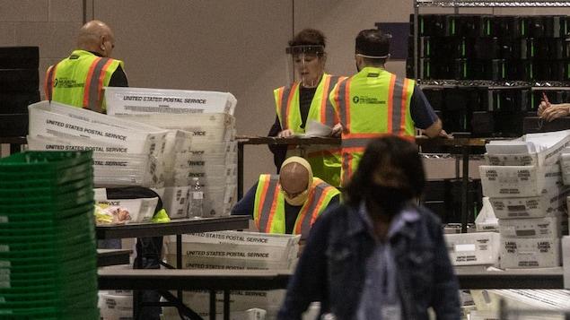 Des gens portant des masques ou des visières dépouillent des bulletins de vote dans une grande salle.